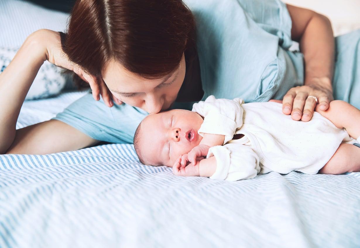 Pieni vauva nukkuu turvallisesti pelkällä patjalla, kasvot vanhemman kasvojen korkeudella. Kuva: iStockphoto