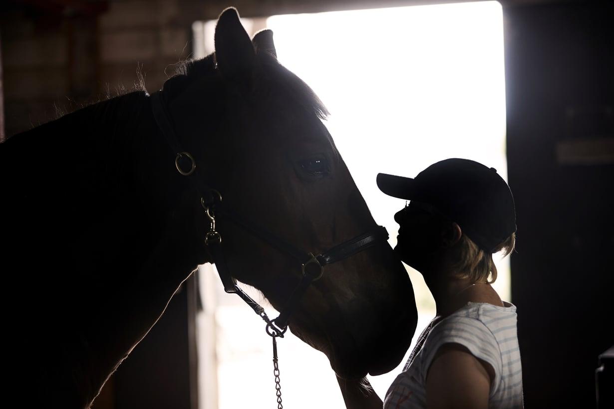 """Tallilla käyminen auttaa Millaa toipumaan. """"Hevosen harjaaminen saa oloni aina paremmaksi."""" (Kuva: Juha Salminen)"""