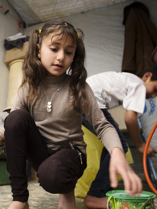 """10-vuotias Wajd leikkimässä Zaatarin pakolaisleirissä vuonna 2014. Taustalla pikkuveli Ariad. Zaatari on suurin syyrialaispakolaisten asuttama leiri, jossa asui vuoden 2018 lopussa yli 78 000 ihmistä. Lähes 20 prosenttia heistä oli alle 5-vuotiaita lapsia. Kuva: <span class=""""photographer"""">Rio Gandara / Sanoma-arkisto</span>"""